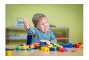 Boy at table with blocks holding one hand up and crying