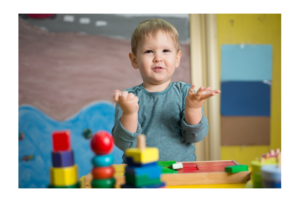 Boy standing at table with nesting toys holding hands up in air with questioning look