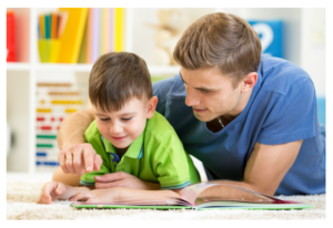 man reading book to young boy