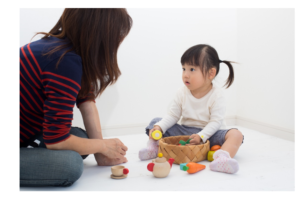 mom and daughter sitting on floor together playing with basket of toys